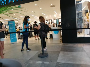 Portimao, Faro, Portugal. Circa 06 01 2020.  Shoppers waiting in a queue to enter the Primark store on 1st day of opening due to lockdown easing. Primark assistant applying alcohol gel to prevent spread of covid 19 virus.