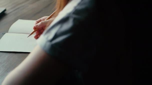 Womans kezét felhívni egy ceruzát papíron közelről