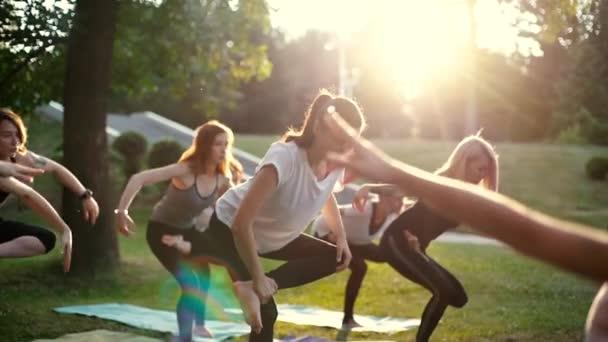 Gruppe junger Frauen in Sportbekleidung steht in Yoga-Stellung auf einem Bein