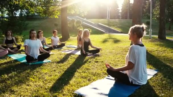 Group of mixed age women is practicing yoga and meditating in park while sunrise