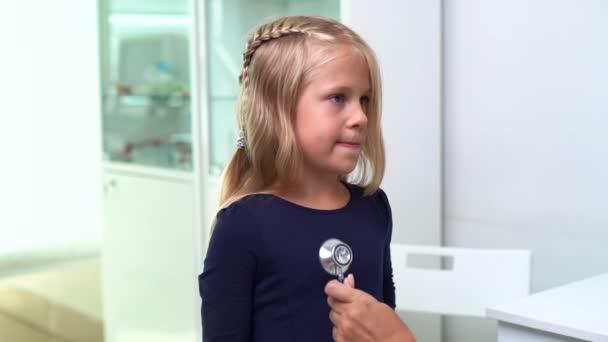 Kinderarzt mit Stethoskop untersucht kleines Mädchen mit blonden Haaren