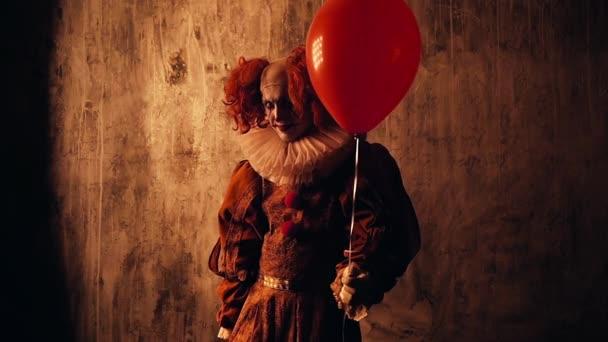 Ijesztő bohóc színes sminkkel karneváli jelmezben bemegy a sötétségbe..