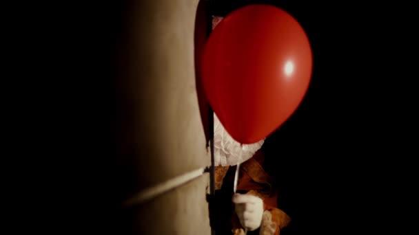 Ijesztő bohóc őrült mosollyal áll egy sötét szoba sarkán.