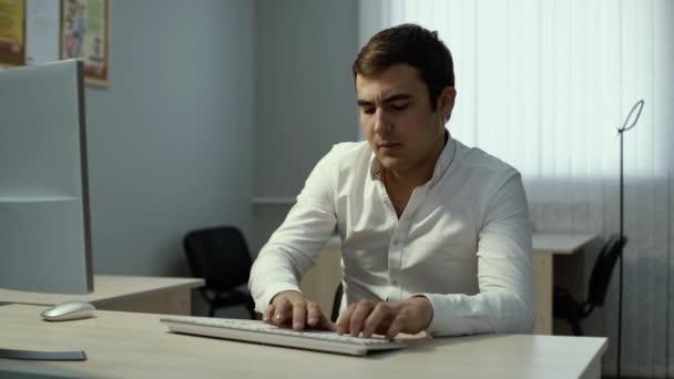 Fáradt üzletember gépel a billentyűzeten, kényelmetlenül érzi magát a szemében, és masszírozza őket.