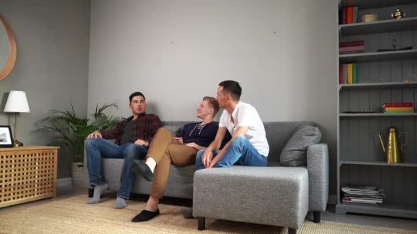 drei fröhliche junge Kerle sitzen zu Hause auf der Couch und unterhalten sich