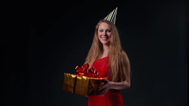 Aranyos fiatal nő ünnepi sapkában tart egy ünnepi dobozt ajándékkal.