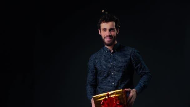 Jóképű fiatalember szakállal tartja üdülési doboz ajándékkal.