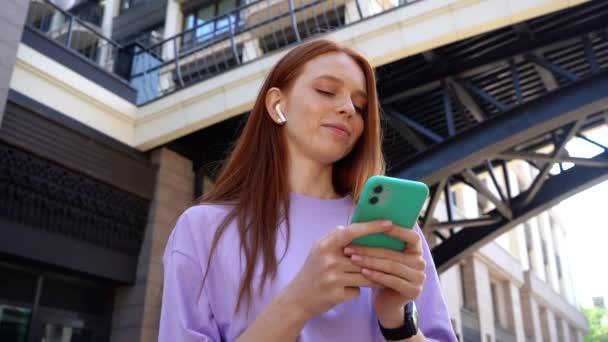Joyful pretty redhead girl with closed eyes listening music using wireless headphones in city street