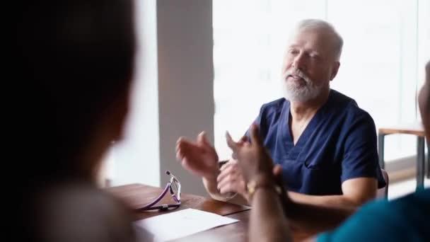 Nahaufnahme des reifen Chefarztes, der die Glückwünsche des erfolgreichen Ärzteteams entgegennimmt.