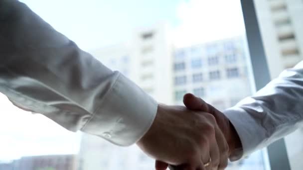 Detailní záběr potřesení rukou dvou partnerů Afroameričan obchodník a kavkazský podnikatel.