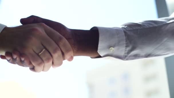 Detailní potřesení rukou dvou nerozpoznatelných partnerů Africký podnikatel a kavkazský podnikatel.