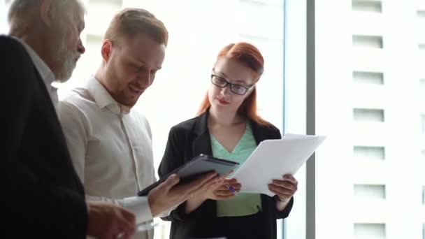 Geschäftsteam aus Geschäftsleuten und Geschäftsfrauen betrachtet digitale Tablet- und Diskussionsdokumente.