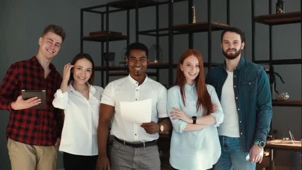 Portrait of cheerful diverse business team standing together in office, looking at camera.