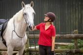 eine attraktive, fröhlich lächelnde junge Frau in einem roten Poloshirt, die ihr weißes Pferd ansieht und lächelt, bereit für einen Ritt