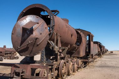 A view along the side of a rusting steam train and carriages slowly rot away at the train graveyard just outside of Uyuni, Bolivia