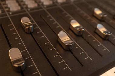 A close up of silver-coloured sliders on a mixing desk in a music studio