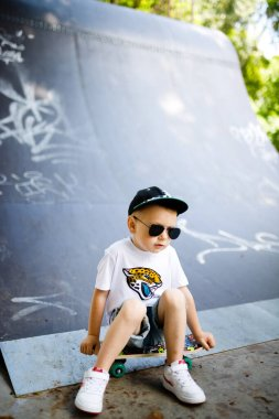 Boy with a skate in a skate park. The boy is sitting on a skateboard.