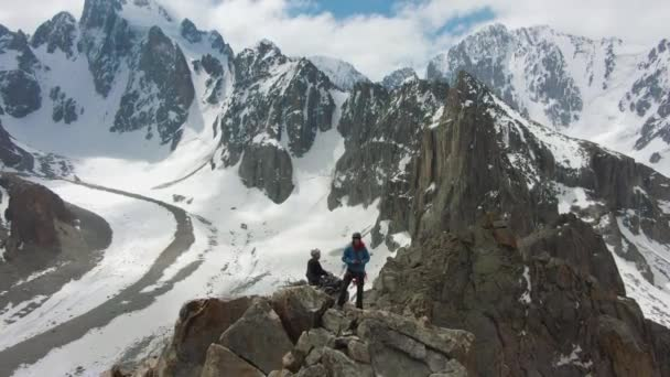 Two Climbers on Peak of Rock. Snow-Capped Mountains. Aerial View