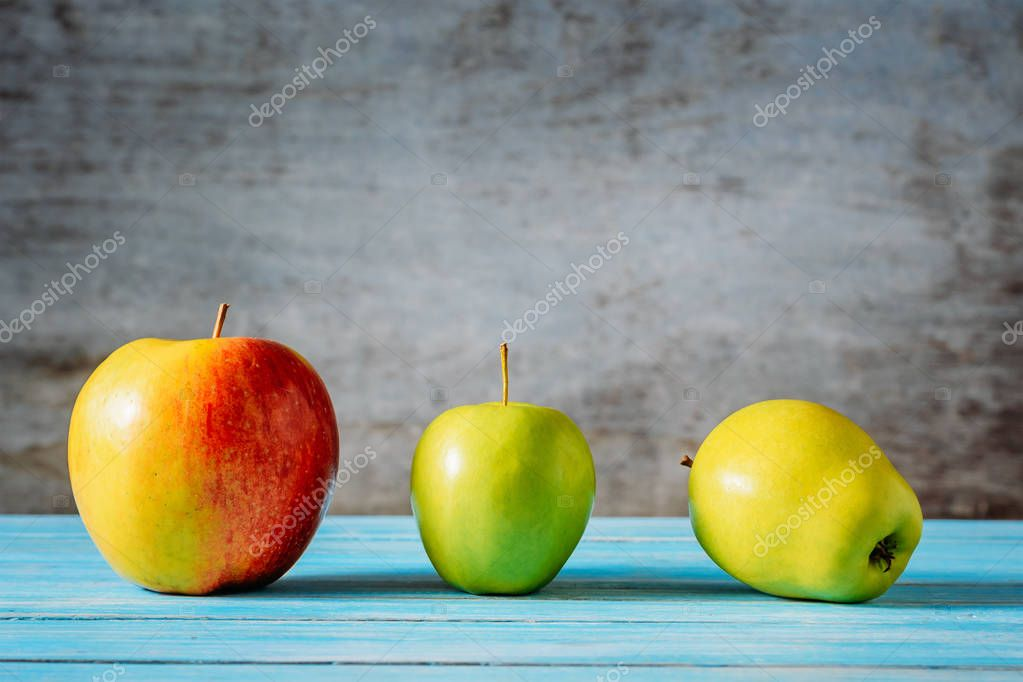 Three different apples on wooden table