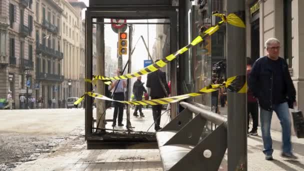 broken and burnt bus stop in barcelona during mass protests