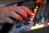 Close-up of the sound engineers hand on the mixer