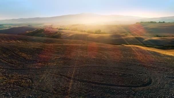 Mozgó légi felvétel a betakarított mezőkre, fákra és hegyekre. Nagyszabású néző gyönyörű színek, megvilágított a lenyugvó nap.