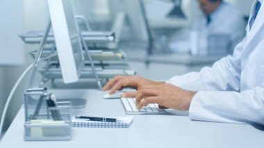 Close-up of Medical Practitioner's Hands Typing on a Keyboard Working on His Desktop Computer. In Background Assistant is Working.