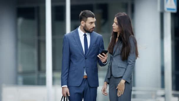Obchodní žena a obchodní muž používání Smartphone a diskuse na rušnou ulici velké město. Obě vypadají nádherně stylová.
