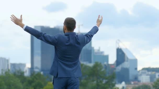 Šťastný, že úspěšné obchodní muž zvedá ruce, má své podnikání vítězství. V pozadí velké město s mrakodrapy.
