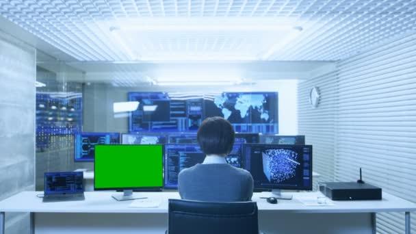 Zadní pohled na IT technik, který pracuje na pomocí neuronové sítě na jeho osobním počítači s Mock-up zelená obrazovka. Pracuje ve velké systém řízení datového centra s více monitory zobrazující grafiku