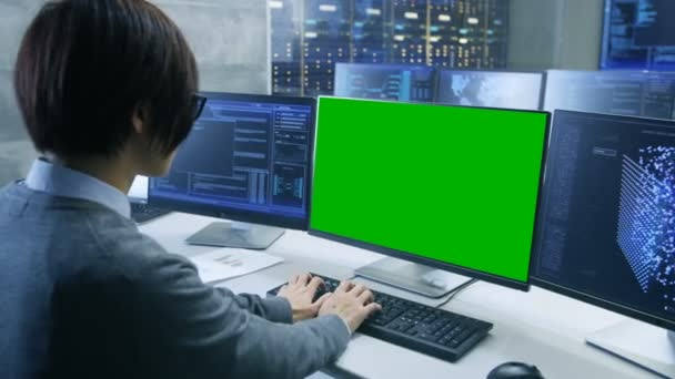Technical Controller/ Operator Working at His Workstation with Multiple Displays with Mock-up Green Screen. Possible Power Plant/ Airport Dispatcher/ Data Center/ Government Surveillance/ Space Program Scenario.