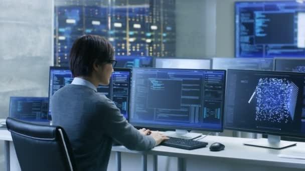 V řídící místnosti systém technické operátor pracuje na svém pracovišti s více monitory zobrazující grafiku. To projektu technik pracuje na umělé inteligenci, velké objemy dat dolování, neuronové sítě.