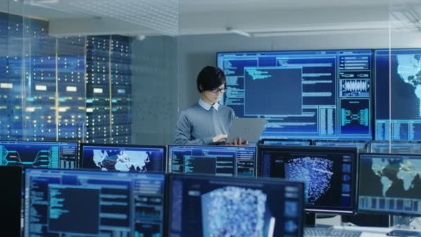 In the System Control Room IT Technician Holds and Works on a Laptop, in Background Multiple Displays with Graphics. Facility Works on Artificial Intelligence, Big Data Mining, Neural Network, Surveillance Project.