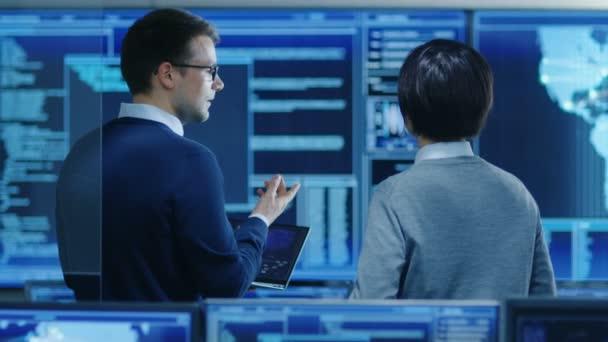 V systému řízení místnosti It Specialist a projektu inženýr mají diskuse při držení notebooku jsou obklopeni více monitorů s grafikou. Pracují v datovém centru na dolování dat, umělá inteligence a neuronové sítě.