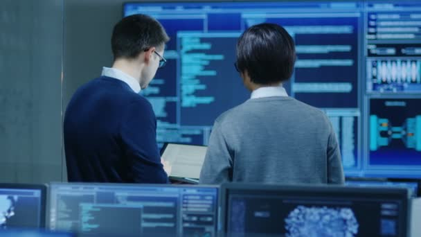 In the System Control Room IT Specialist and Project Engineer Have Discussion while Holding Laptop, theyre surrounded by Multiple Monitors with Graphics. They Work on Data Mining, AI and Neural Networking.
