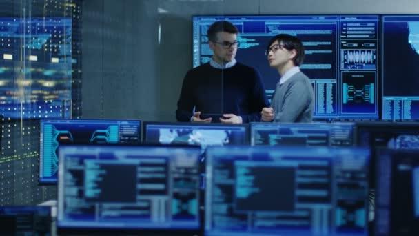 V systému řízení místnosti projekt řídit a to inženýr mají diskuse jsou obklopeni více monitorů s grafikou. Pracují v datovém centru na dolování dat, umělá inteligence a neuronové sítě