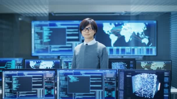 In the System Control Room Smart Engineer Smiles and Makes Thinking Gesture. High-Tech Facility Has Multiple Monitors with Graphics.