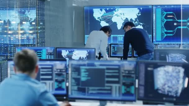 In the System Control Room Project Manage and IT Engineer Have Discussion, theyre surrounded by Multiple Monitors with Graphics. Big Monitor Shows Interactive Logistics Map.