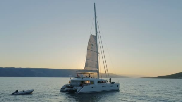 Aerial Shot of a Sailing Catamaran Yacht with Raised Sail Traveling Through The Calm Seas with Sun Rising from Behind the Hills.