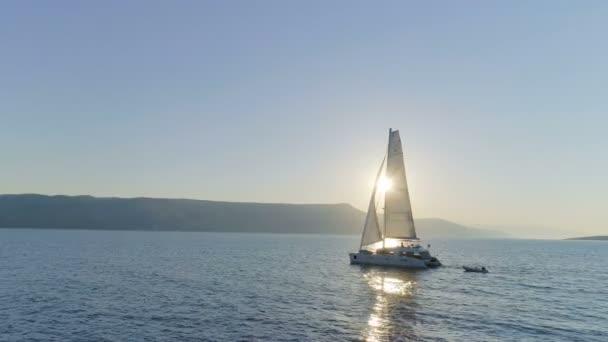 Letecký snímek Long plachtění katamarán Yacht s zvedl plachtu cestování přes moře klidu se sluncem stoupá s pobřežních kopcích, které jsou viditelné. Lidé na dovolené na palubě.