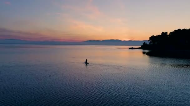 Aerial Shot of a Beautiful Woman with on a Standup Paddleboard. Woman Silhouette with Pink Sunset and Coastal Hills Visible