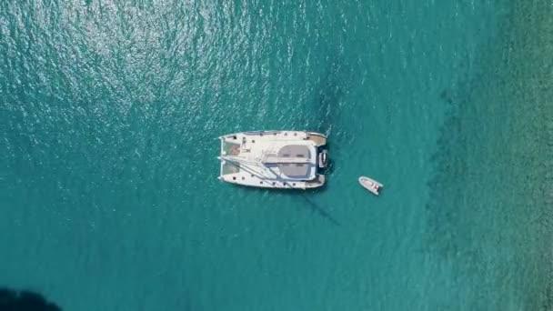 Letecký shora dolů pohled katamarán jachty kotvící s opalováním lidé na jeho palubě. Loď stojí v Azure mořských vodách s korálovým útesem viditelné