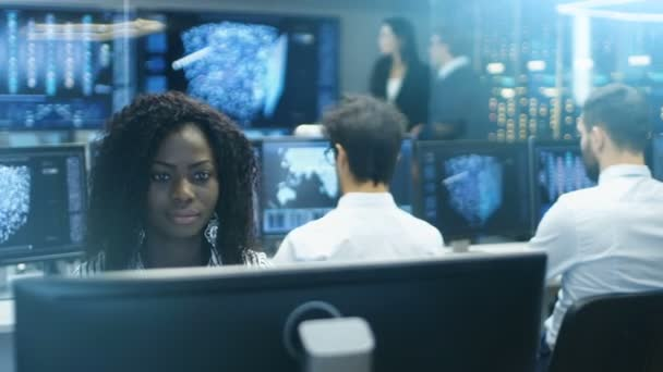 Female Computer Engineer Works on a Neural Network/ Artificial Intelligence Project with Her Multi-Ethnic Team of Specialist. Office Has Multiple Screens Showing 3D Visualization.