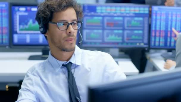 Zástupce služeb podpory zákazníků hovoří s klientem prostřednictvím sluchátek s mikrofonem. Pracuje ve velké technické poradenské společnosti