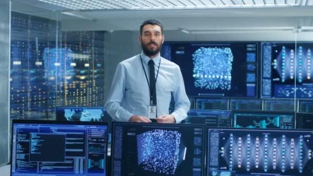 In der Forschungseinrichtung für künstliche Intelligenz spricht der Wissenschaftler über sein Projekt in die Kamera. Hintergrund zeigt Bildschirme mit futuristischem High-Tech-Design.