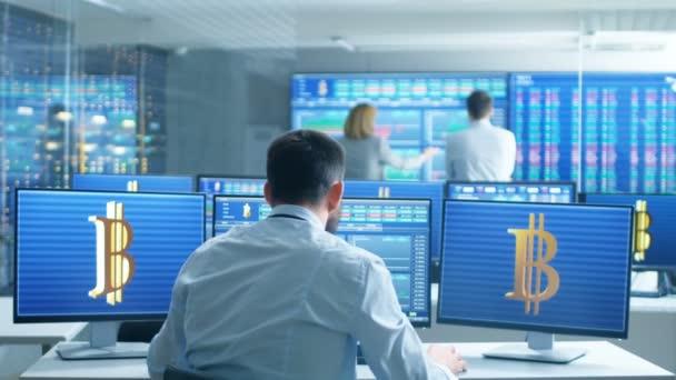 Pohled zezadu akcií obchodníka lomil rukama ve velkých vítězství, on pracuje pro oddělení výměny kryptoměn. Obrazovky zobrazují relevantní Data, grafy a čísla telegraf, ostatní lidé pracují v kanceláři