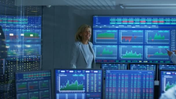 Top Manager Enters Stock Market Operating Room Greeting Traders and Brokers. Room is Full of Monitor Showing Relevant Ticker Numbers and Graphs.
