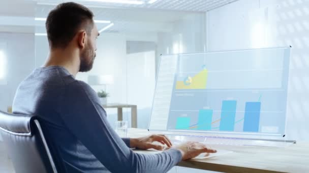In the Near Future Office Worker Designs Report on His Transparent Computer Display. Screen Show Interactive User Interface with Statistics, Graphs and Charts. Office is Bright and Modern.