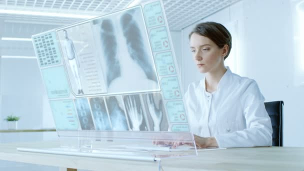 In the Near Future Beautiful Female Doctor Works on Transparent Computer Display. Screen Shows Patient with Full Medical History, X-ray and Test Results.