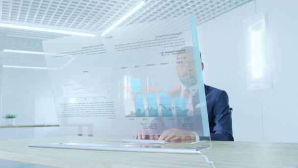 In the Near Future Successful Businessman Works on Computer with Transparent Display that Shows Interactive Line Charts and Other Useful Information. His Office is Bright and Modern.